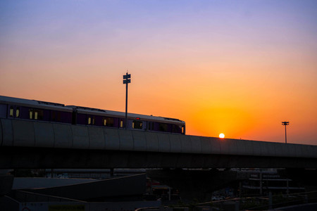 silhouette of sky train is running on the evening