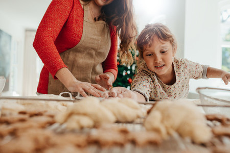 Little girl helping her mother in making cookies for  Christmas