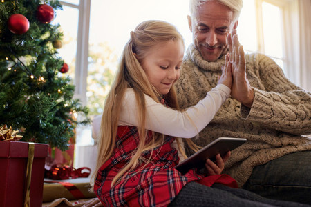 Little girl with grandfather using digital tablet at home