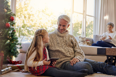 Little girl and grandfather by christmas tree with tablet pc