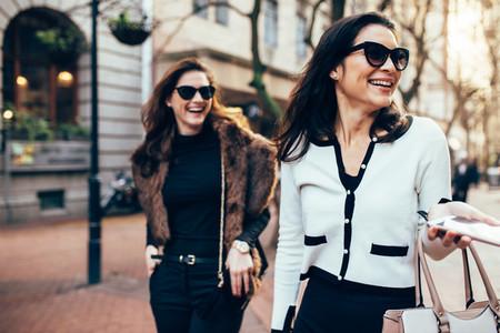 Two women on city street having fun