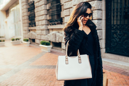 Woman with shopping bags and talking on mobile phone
