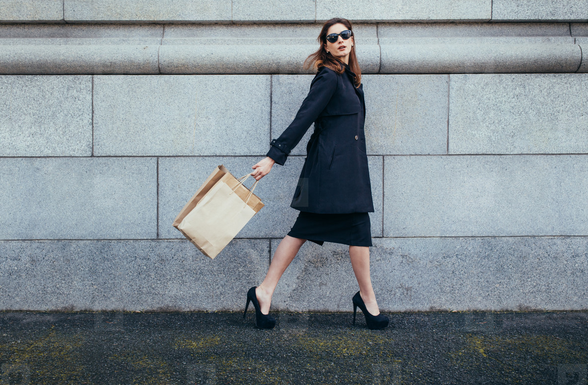 Stylish female shopper walking with shopping bag