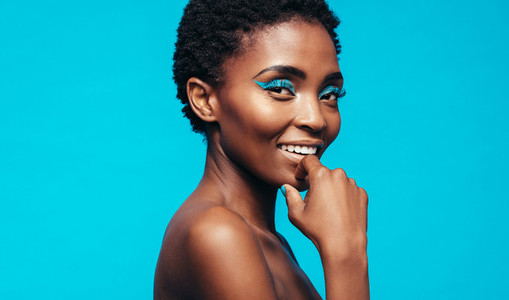 Woman with makeup smiling against blue background