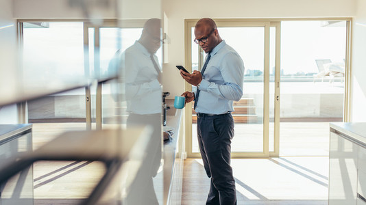 Businessman checking mobile phone while having breakfast