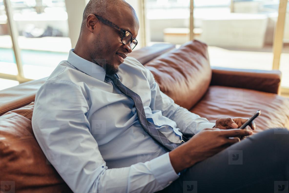 Businessman sitting on lounge using mobile phone