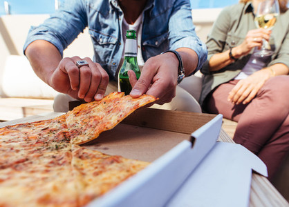 Friends eating pizza on rooftop party