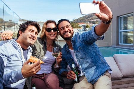 Young friends taking selfie on a rooftop party
