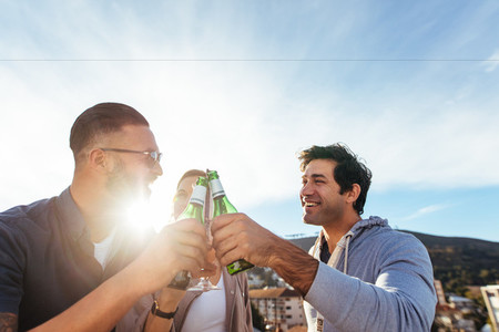Group of friends toasting beers at rooftop party