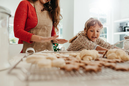 Mother teaching daughter to make cookies for Christmas