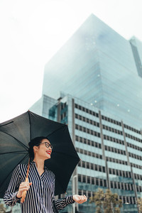Smiling woman outdoors in the city with umbrella