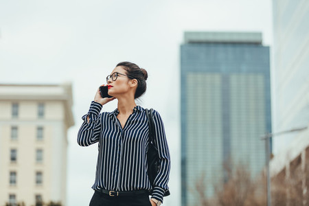 Businesswoman walking outdoors with cellphone