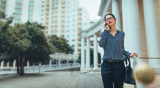 Businesswoman walking outdoors using mobile phone