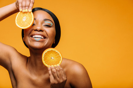 Black woman with healthy skin and orange slices