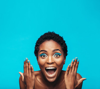 Excited young woman with vibrant makeup