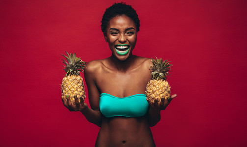 Happy african woman holding fresh pineapples