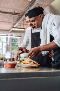 Chefs preparing food together in restaurant kitchen