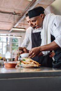 Chefs preparing food together in restaurant kitchen