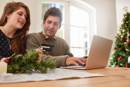 Couple shopping online with credit card for Christmas