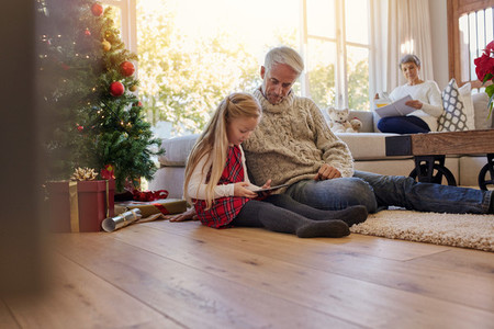 Little girl with grandfather using digital tablet at home during