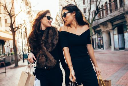 Women with shopping bags walking along the city street