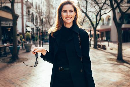 Stylish female with sunglasses walking on city street
