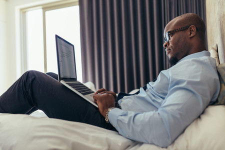Businessman working on laptop computer lying on bed