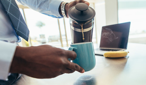Man pouring hot coffee in a mug