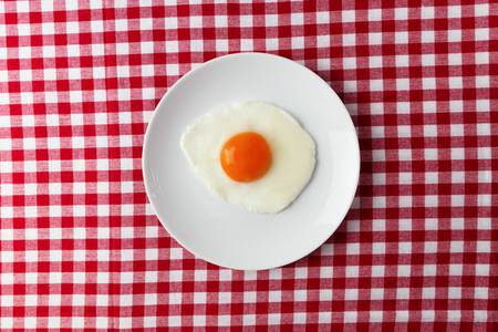 Fried egg overhead on plate on breakfast tablecloth
