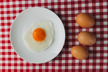 Fried eggs overhead on plate on breakfast tablecloth