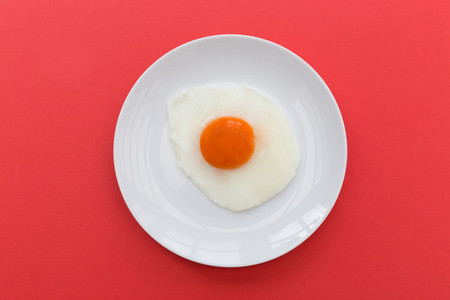 Fried egg and yoke overhead on plate and red background