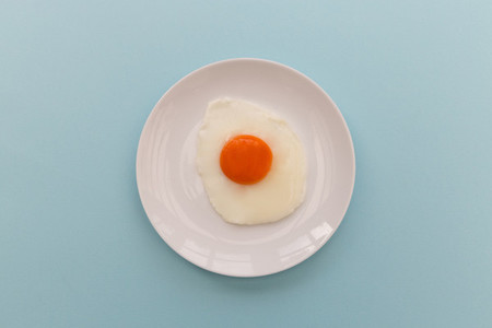 Fried egg and yoke overhead on plate and blue background