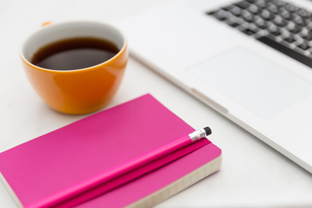 Yellow coffee cup and bright pink notebook in modern office
