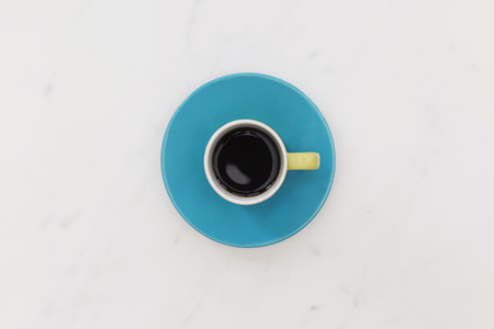 Coffee cup and saucer on white marble background