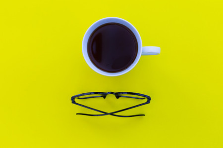Eyeglasses and coffee cup overhead on yellow background