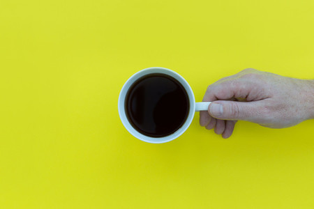 Hand holding coffee cup overhead on yellow background