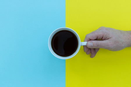 Hand holding coffee cup overhead on blue and yellow background