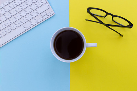 Computer keyboard and coffee cup overhead on blue and yellow bac