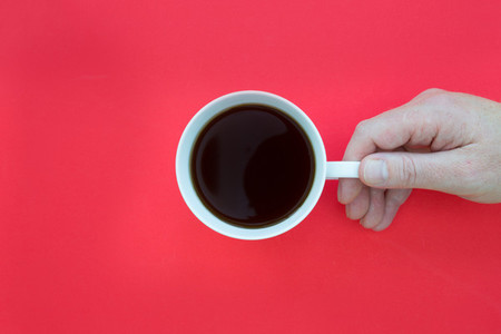 Hand holding coffee cup overhead on red background