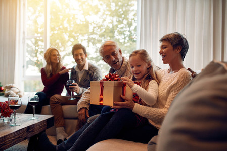 Little girl sitting in living room with family opening christmas