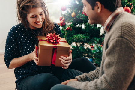 Young couple exchanging Christmas gifts at home