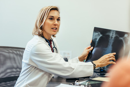 Doctor showing diagnosis of x ray image to patient