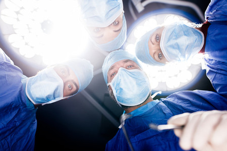 Surgeons under surgery lights in operating theatre