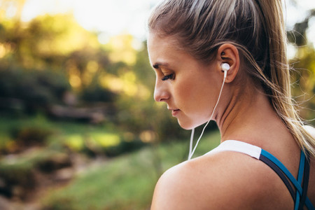 Woman runner wearing earphones during workout