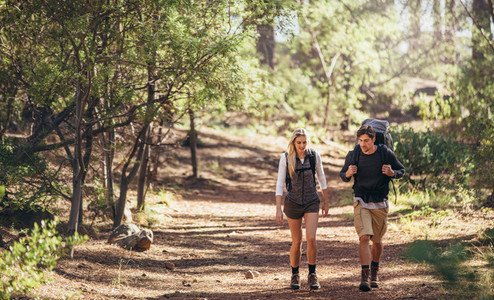 Hiking couple walking in forest wearing backpacks
