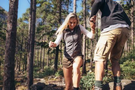Hiking couple walking on rocks in forest wearing backpacks