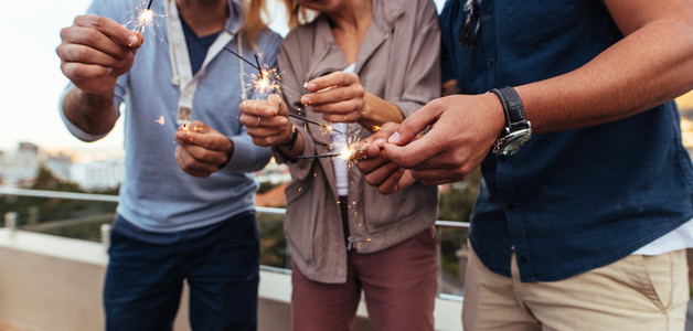Friends holding sparklers on rooftop party