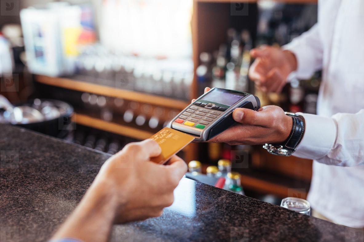 Customer making payment using credit card at bar