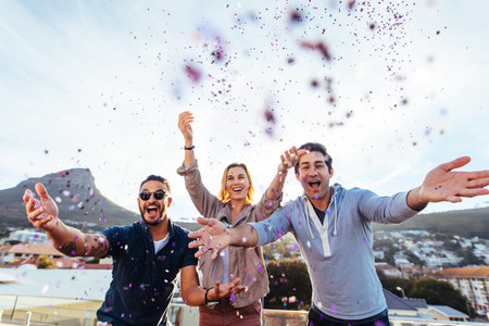 Group of friends enjoying party with confetti