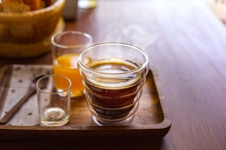 Hot americano coffee with orange juice on wooden table